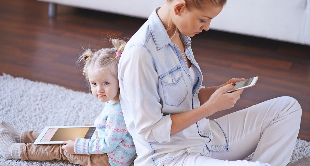 Little girl and young woman with gadgets sitting back to back on the floor